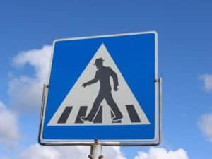 A pedestrian crossover sign with sky as background