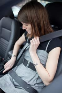 Road safety concept young woman fastening her seat belt